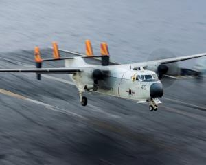 The propeller-powered transport plane, a C-2 Greyhound, carries personnel, mail and other cargo...
