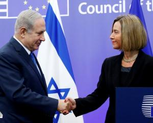 Israeli Prime Minister Benjamin Netanyahu shakes hands with EU foreign policy chief Federica...