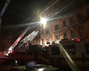 New York Fire Department ladder trucks deploy at a building fire in the Bronx borough of New York...