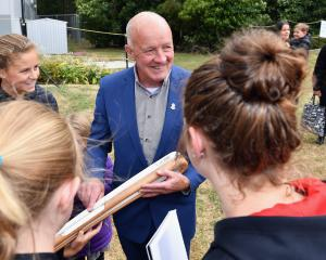 Dick Tayler hands the Commonwealth Games Queen's Baton to children at Jellie Park in Christchurch...
