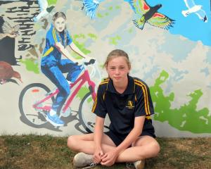Alexandra Primary School pupil Ruby Nevill (12) sits beside Rail Trail Bird Girl, a mural she and...