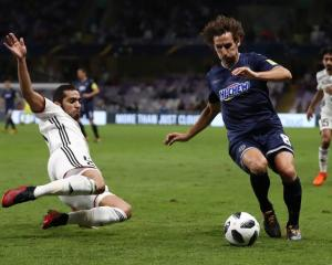 Musallem Fayez of Al-Jazira tackles Albert Riera of Auckland City in their match this morning....