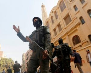 Security forces stand guard at the site of attack on Mar Mina church in Helwan district on the...
