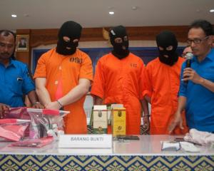 Anti-Narcotics Agency officials show an Australian man, an American man, and a Malaysian man to...