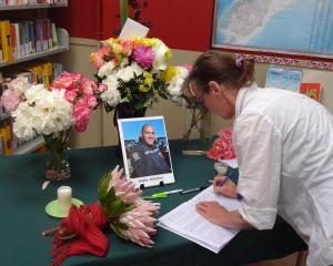 Palmerston woman Nell Collyer signs a condolence book at the East Otago High School library...