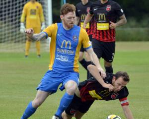 Southern United's Danny Ledwith competes for the ball as Canterbury United's  Gary Ogilvie falls...