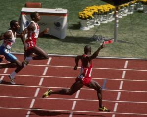 Canadian Ben Johnson celebrates as he crosses the finish line ahead of American Carl Lewis and...
