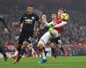 Arsenal's Nacho Monreal tries to control the ball under pressure from Manchester United's Antonio...