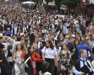 University of Otago graduands are joined by family and friends as they march down George St  to...