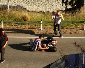 Members of the public help an injured motorcyclist in Fernhill Rd, Queenstown, last night. Photo:...