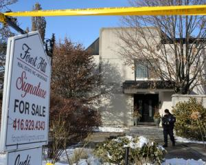 A police forensics photographer works outside the home of billionaire founder of Canadian...