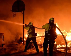 Firefighters battle flames from a Santa Ana wind-driven brush fire called the Thomas Fire. Photo:...
