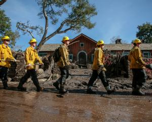 Rescue workers enter properties to look for missing persons after a mudslide in Montecito,...