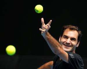 Roger Federer laughs as he serves during a practice session before the Australian Open. Photo:...