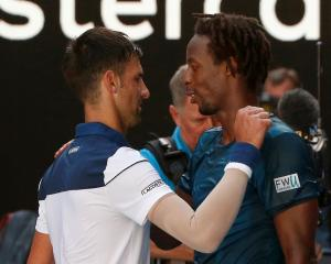 Novak Djokovic (L) and Gael Monfils embrace after their match. Photo: Reuters