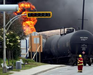 A firefighter walks past a burning wagon at the scene of the accident in July 2013. Photo: Reuters