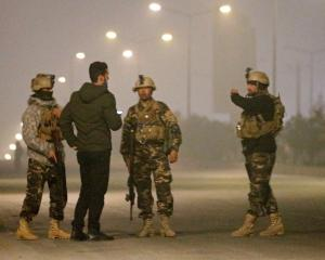 Afghan security forces keep watch near the site of an attack on the Intercontinental Hotel in...