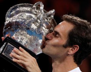 Roger Federer celebrates with the trophy after his victory in the Australian Open. Photo Reuters