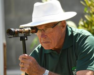 Bowls umpire Colin McKenzie uses a boundary scope at the Kaikorai greens during the national...