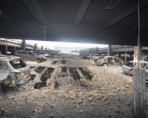 Burnt cars are seen in what remains of the multi-storey car park, where a large fire destroyed...