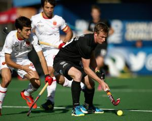 Black Sticks striker Hugo Inglis (right) holds off Marc Serrahima, of Spain, in a Hockey World...