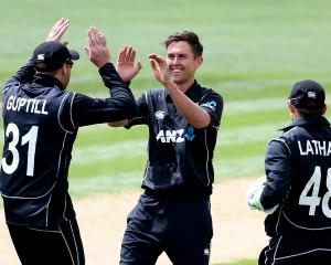 New Zealand paceman Trent Boult (centre)  is congratulated by team-mates Martin Guptill (left)...