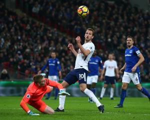 A familiar sight: Tottenham Hotspurs' Harry Kane guides the ball past Everton's Jordan Pickford...