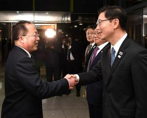South Korean Vice Unification Minister Chun Hae-Sung, (R) shakes hands with the head of North...
