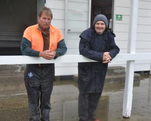 A dejected Kumara Racing Club acting president Patrick Meates, left, stands in water with the...