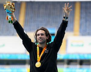 Newly-retired Kiwi blade runner Liam Malone celebrates on the podium after winning a gold medal...