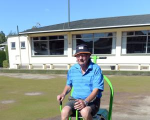 North East Valley Bowling Club greenkeeper Neill Williams rolls the barren-looking playing...
