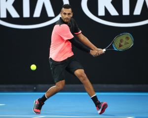Nick Kyrgios plays a backhand in his second round Australian Open match last night. Photo: Getty...