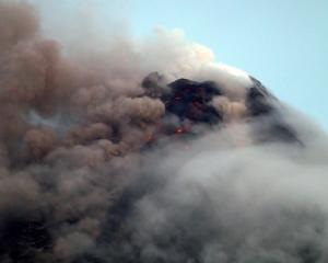 Clouds partially cover Mayon volcano's crater as it spews a column of ash during another mild...