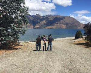 The parents and brother of missing American man Tyler Nii look across Lake Wakatipu from the...