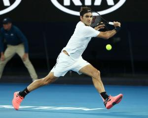 Roger Federer reaches for a backhand during his opening round Australian Open match last night....