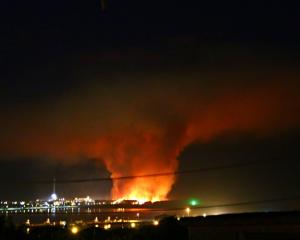 The night sky is lit up by a scrub fire that is still burning near Tiwai Pt in Southland. Photo:...