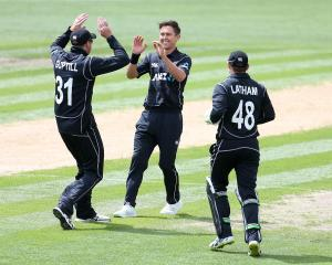 Martin Guptill, Trent Boult and Tom Latham of New Zealand celebrate the dismissal of Fakhar Zaman...