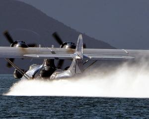 A Catalina flying boat, which will return this year, hurtles towards boats on Lake Wanaka as it...