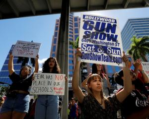 Protesters hold placards at a rally calling for more gun control in the wake of the shooting at...