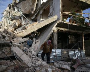 A person looks at damage to a building in the besieged town of Douma, Eastern Ghouta. Photo Reuters