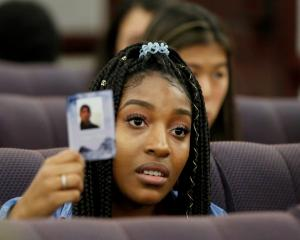 Marjory Stoneman Douglas High School pupil Tyra Hemans holds a photo of her friend Joaquin Oliver...