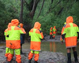 Members of the Fiordland Search and Rescue team  scour the Manuherikia River for missing...