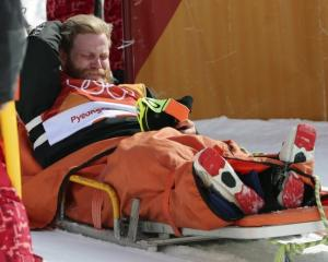 Byron Wells reacts after injuring himself before the men's ski halfpipe final at the Winter...