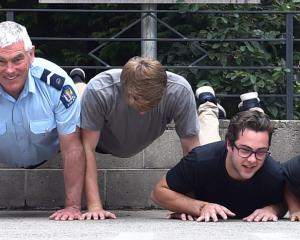 Campus cop Senior Constable John Woodhouse tests his brawn against first-year students at...