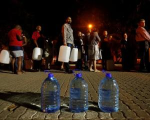 People queue to collect water as fears over the city's water crisis grow in Cape Town. Photo:...
