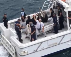 People are taken to the shore by a police boat from an Australian cruise ship after a brawl, at...
