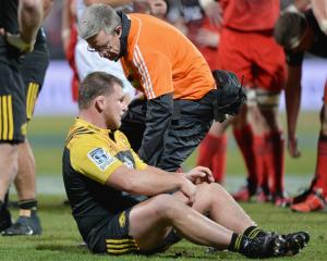 Reggie Goodes of the Hurricanes is assisted from the field after a concussion during a Super...