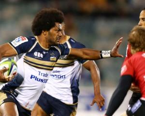 Brumbies winger Henry Speight sticks an arm out to keep off defenders against the Lions last...