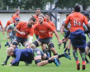 Highlanders loose forward Luke Whitelock (centre) tries to make an impact as Elliot Dixon (left)...