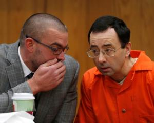 Larry Nassar, a former team USA Gymnastics doctor, talks with his defense attorney Matt Newburgh...